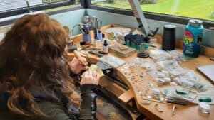 Stephanie working at her light-filled bench overlooking the garden